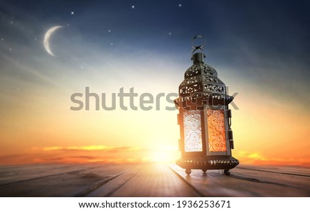 Ornamental Arabic lantern with burning candle glowing at night. Festive greeting card, invitation for Muslim holy month Ramadan Kareem. Royalty-Free Stock Photo #1936253671