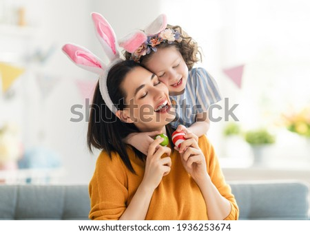 Happy holiday! Mother and her daughter with painting eggs. Family celebrating Easter. Cute little child girl is wearing bunny ears.  Royalty-Free Stock Photo #1936253674