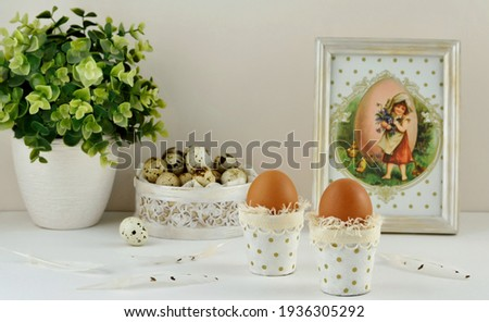 Decorative easter composition with eggs in a pots, easter picture in a frame, houseplant and quail eggs in a pattern box on white table.