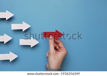 Many white arrows follow one red arrow. Symbol of following the leader straight to the goal Royalty-Free Stock Photo #1936356349
