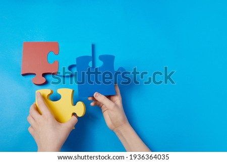 Top view hands of a autistic child arranging color puzzle symbol of awareness for autism spectrum disorder. Autism Awareness Day or month.