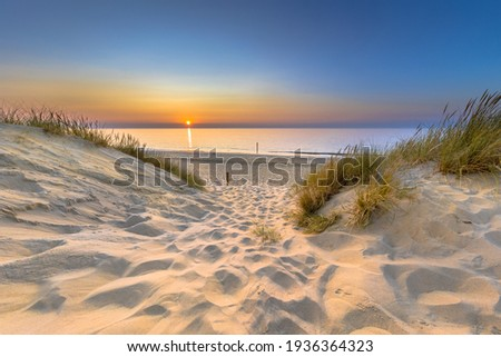 Inviting Sunset View over ocean from dune over North Sea and Canal in Ouddorp, Zeeland Province, the Netherlands. Outdoor scene of coast in nature of Europe. Royalty-Free Stock Photo #1936364323