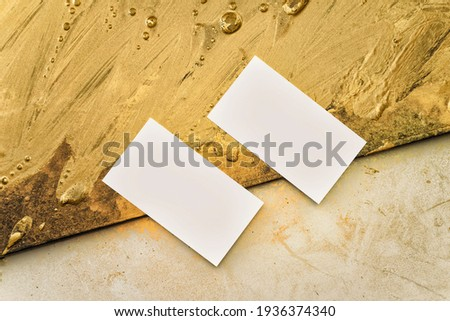 Two business cards for art director on the background from gold painting and a workplace for creativity. Gold strokes, abstraction
