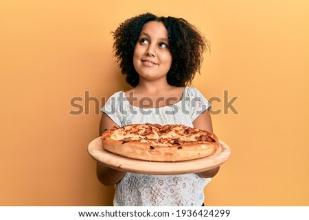 Young little girl with afro hair holding italian pizza smiling looking to the side and staring away thinking.  Royalty-Free Stock Photo #1936424299