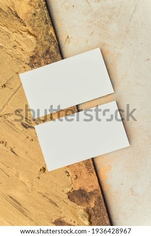Two business cards for art director on the background from gold painting and a workplace for creativity. Gold strokes, abstraction. Branding, identity