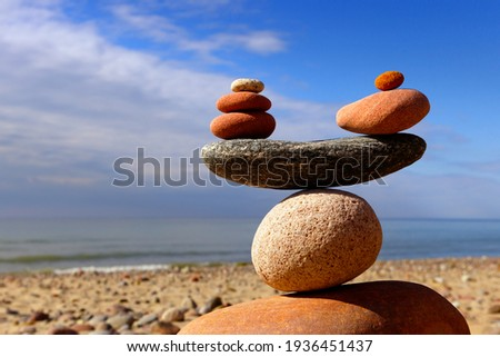 Symbolic scales of stones on the background of the sea and blue sky. Concept of life balance and harmony. Pros and cons concept