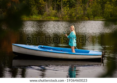 A woman riding on the back of a boat in a body of water
