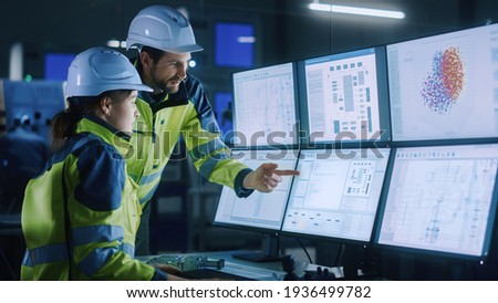 Industry 4.0 Modern Factory: Chief Project Manager Talks to Female Engineer, She Points at Computer Screens Showing Complex Industrial Electronics Design Blueprints, They Have Find Problem Solution Royalty-Free Stock Photo #1936499782