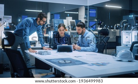 Factory Office Meeting Room: Team of Engineers Gather Around Conference Table, They Discuss Project Blueprints, Inspect Mechanism, Find Solutions, Use Laptop. Industrial Technology Factory Royalty-Free Stock Photo #1936499983