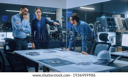 Factory Office Meeting Room: Team of Engineers Gather Around Conference Table, They Discuss Project Blueprints, Inspect Mechanism, Find Solutions, Use Laptop. Industrial Technology Factory Royalty-Free Stock Photo #1936499986