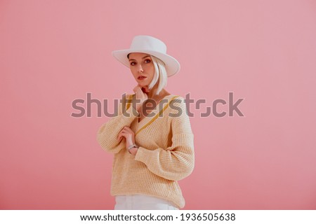 Elegant woman wearing trendy yellow v-neck sweater, stylish silver wrist watch, white hat, posing on pastel pink background. Spring fashion conception. Copy, empty space for text
