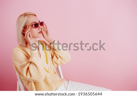 Elegant woman wearing trendy pink sunglasses, yellow v-neck sweater, posing on pastel pink background. Spring fashion conception. Copy, empty space for text