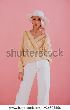 Elegant fashionable model wearing trendy yellow v-neck sweater, white jeans, stylish silver wrist watch, white hat, posing on pastel pink background. Spring fashion conception