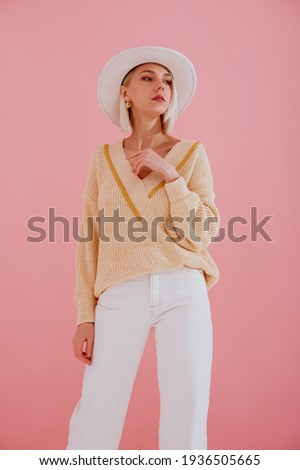 Elegant woman wearing trendy yellow v-neck sweater, white jeans, stylish silver wrist watch, white hat, posing on pastel pink background. Spring fashion conception