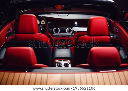 Red with blue cabriolet interior - rear view. The red head restraints of the four seats, front panel of the car, part of the steering wheel, front doors and a windshield with a rear-view mirror. Royalty-Free Stock Photo #1936521106