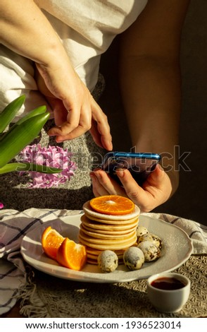 Girl woman takes pictures on her cell phone of a pancake breakfast dessert that she made herself