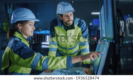 Industry 4.0 Modern Factory: Project Engineer Talks to Female Operator who Controls Facility Production Line, Uses Computer with Screens Showing AI, Machine Learning Enhanced Assembly Process Royalty-Free Stock Photo #1936528474