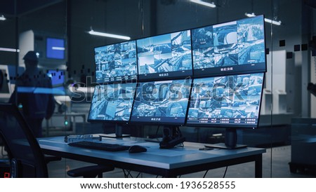Industry 4.0 Modern Factory: Security Control Room with Multipoke Computer Screens Showing Surveillance Camera Footage Feed. High-Tech Security Royalty-Free Stock Photo #1936528555