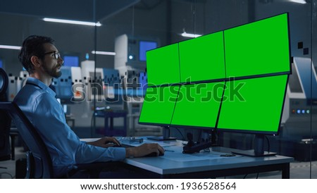 Industry 4.0 Modern Factory: Security Operator Controls Proper Functioning of Workshop Production Line, Uses Computer with 6 Screens Showing Green Screen Mock up Template.