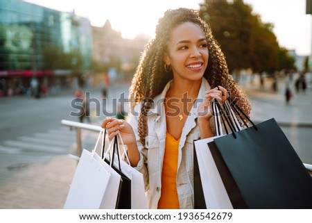 Fashion woman with shopping bags walking on street. Spring Style. Consumerism, sale, purchases, shopping, lifestyle concept. Royalty-Free Stock Photo #1936542679