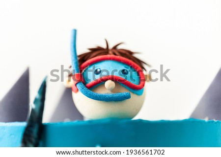 Sea and shark themed cake with blue cream cheese frosting on the white background. Diver in a mask. Snorkelling among the sharks. Funny birthday cake. Danger in the sea. Homemade pastry