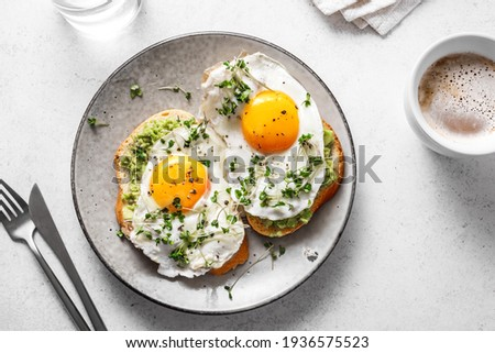 Avocado Egg Sandwiches and coffee for healthy breakfast. Whole grain toasts with mashed avocado, fried eggs and organic microgreens on white table. Royalty-Free Stock Photo #1936575523