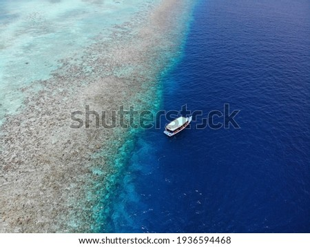 Aerial picture of single white diving boat on turquoise water and Maldivian coral reef. Picturesque scenery. Scuba diving day trip.
