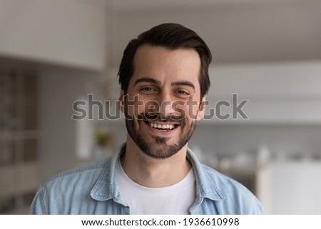 Close up headshot portrait of smiling 30s Caucasian man look at camera posing in own flat or apartment. Profile picture of happy 20s male renter or tenant in new home. Real estate, rental concept.