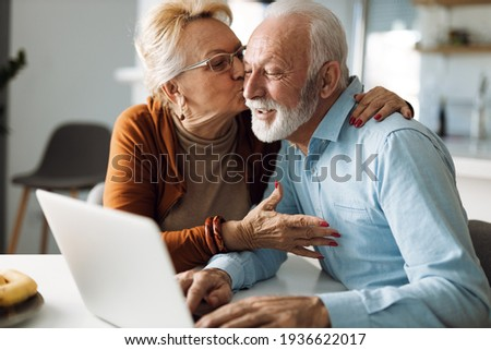 Mature woman kissing her mature husband while he uses a computer at home Royalty-Free Stock Photo #1936622017