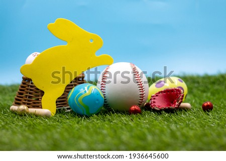 Baseball with Yellow bunny rabbit Easter egg on green grass and blue sky background for Easter Holiday