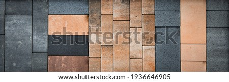 Bricks in different materials and colors stacked into a wall. Usable as background for architecture, building materials. Horizontal banner Royalty-Free Stock Photo #1936646905