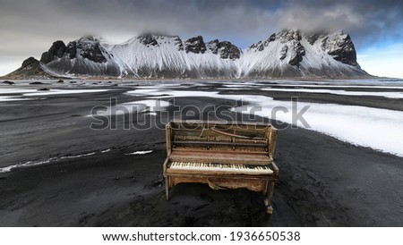 A derelict upright piano washed up on the black sand beach of the Stokksnes peninsula with the majestic, snow-capped Vestrahorn mountains in the background.  Royalty-Free Stock Photo #1936650538