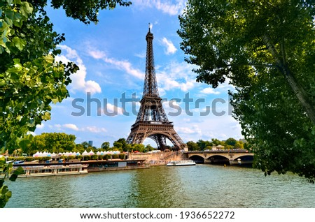 Eiffel Tower, iconic Paris landmark across the River Seine with green leaves vibrant blue sky, France Royalty-Free Stock Photo #1936652272