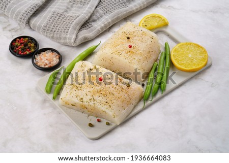 Halibut fish fillet prepared for cooking on cutting board with lemons, peppers and salt