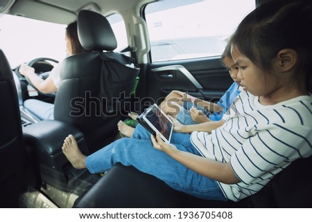 Two asian child girls sitting on backseat and watching cartoon in tablet together while traveling in the car with fun. Childhood and family lifestyles in car concept.