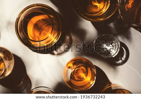 Hard strong alcoholic drinks, spirits and distillates in glasses: vodka, cognac, tequila, scotch, brandy and whiskey, grappa, vermouth, rum. White background with hard lights and shadows, top view Royalty-Free Stock Photo #1936732243