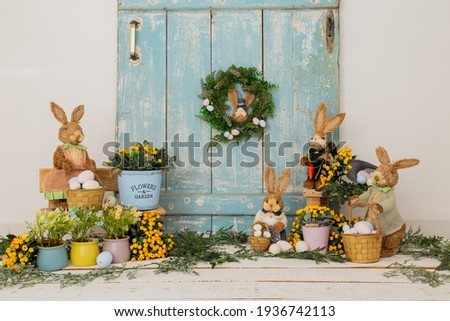 Easter backdrop or background for photo mini session in blue color. Contains straw rabbits and eggs basket. Royalty-Free Stock Photo #1936742113