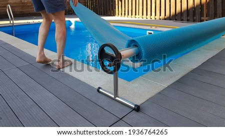Man covers swimming pool with cover for protection against dirt, leaves, heating and cooling water. Royalty-Free Stock Photo #1936764265