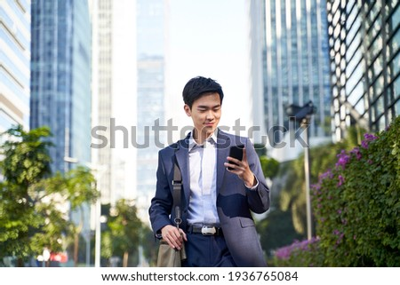 young asian businessman looking at messages on cellphone while walking in the street in downtown of modern city Royalty-Free Stock Photo #1936765084