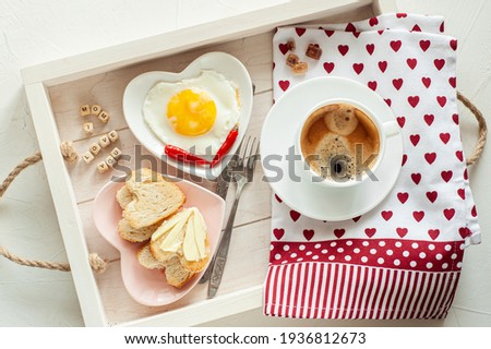 Mother's Day. Breakfast for mom. On the tray there is a cup of coffee, two plates of scrambled eggs and heart-shaped bread and the inscription I Love You Mom. View from above.