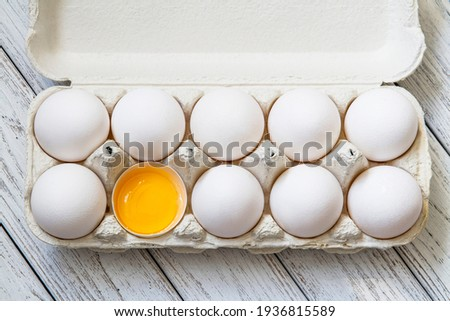 Close-up of fresh white organic chicken eggs in the paper tray and egg yolk on light wooden background. Top view Royalty-Free Stock Photo #1936815589