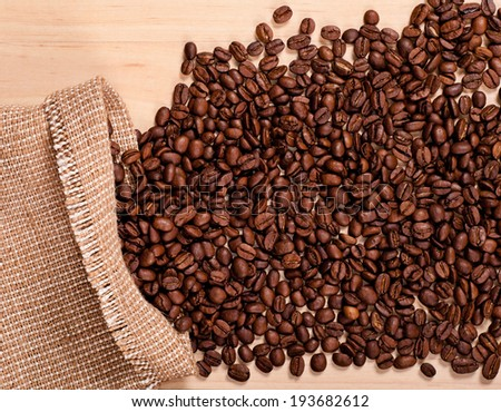 the coffee beans in burlap on wooden background #193682612
