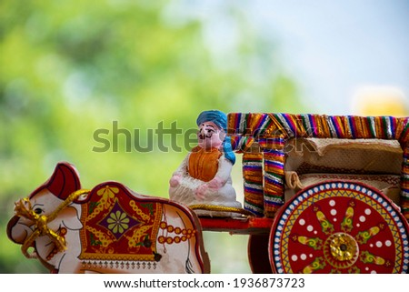 Stock photo of a beautiful traditional Indian wooden bull cart and statue of farmer sitting on bull cart, kept on grains on sunny day at bangalore city karnataka India. blur background.