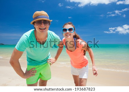 Portrait of happy young couple in bright clothes and sunglasses having fun on tropical beach #193687823