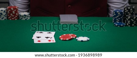 a combination of cards and chips on the green poker table