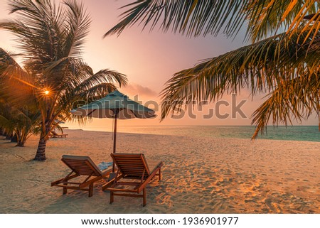 Beautiful tropical sunset scenery, two sun beds, loungers, umbrella under palm tree. White sand, sea view with horizon, colorful twilight sky, calmness and relaxation. Inspirational beach resort hotel Royalty-Free Stock Photo #1936901977