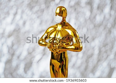 Hollywood Golden Oscar Academy award statue in medical mask on silver background. Success and victory concept. Oscar ceremony in coronavirus time