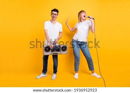 Photo of funny young couple wear white t-shirt spectacles dancing holding boombox singing mic isolated yellow color background