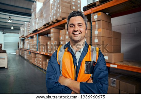Smiling portrait of a male supervisor standing in warehouse with his arm crossed looking at camera Royalty-Free Stock Photo #1936960675