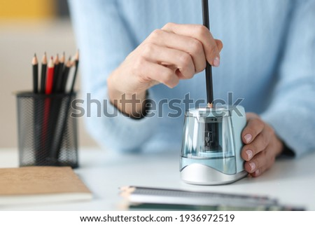 Female hands sharping pencil with electronic sharpener closeup Royalty-Free Stock Photo #1936972519